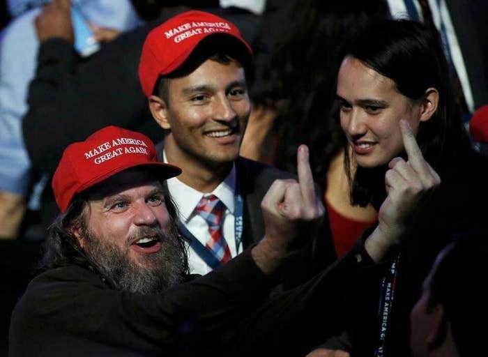 "Two men in ""Make America Great Again"" hats stand next to the CEO of Clearview AI; one of the men in hats holds up two middle fingers"