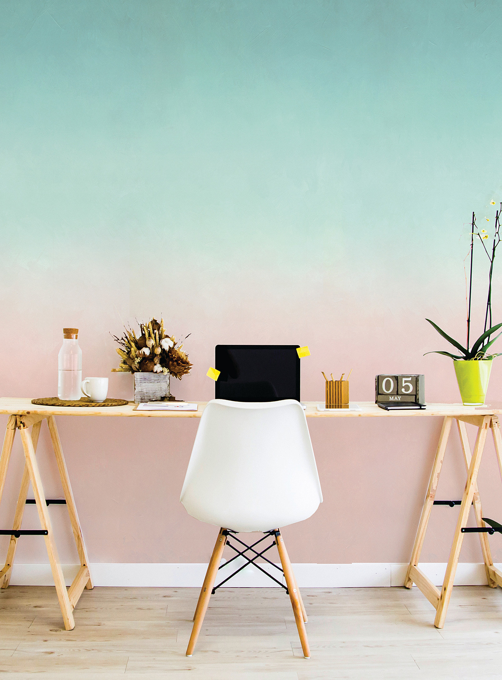 A long desk and chair placed against a large wall covered in wallpaper