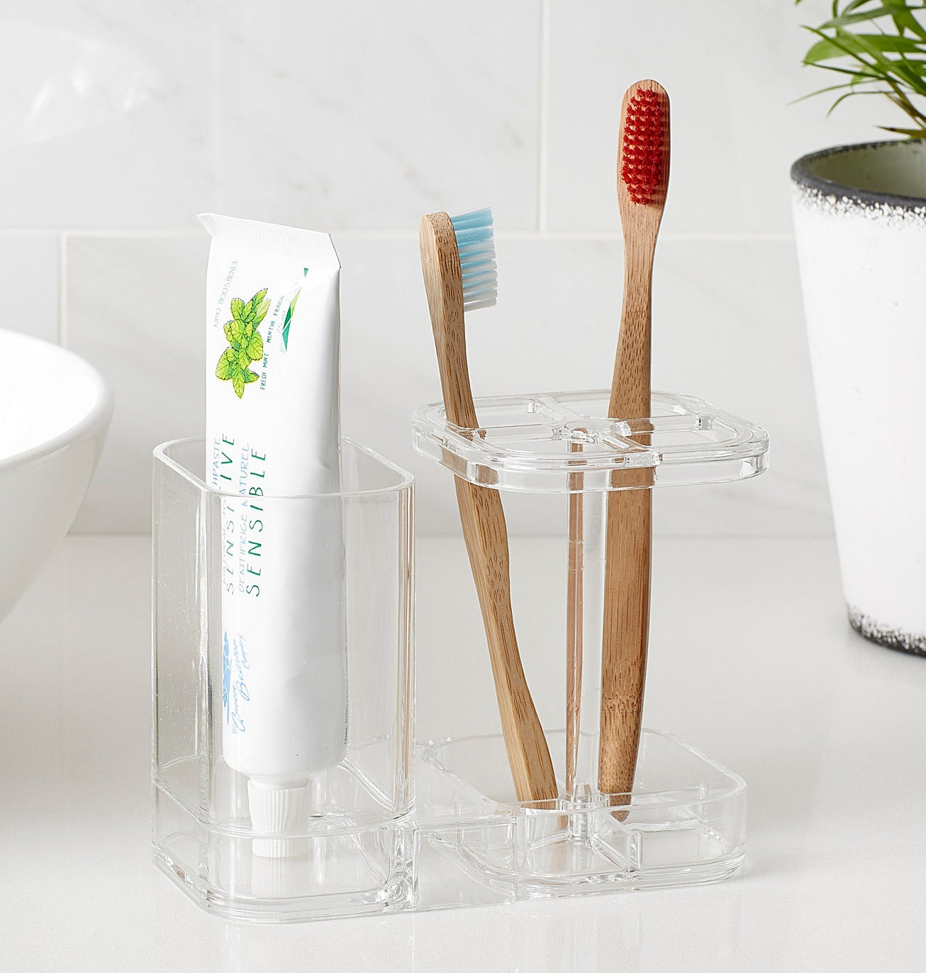 The bathroom organizer with toothbrushes and toothpaste inside of it