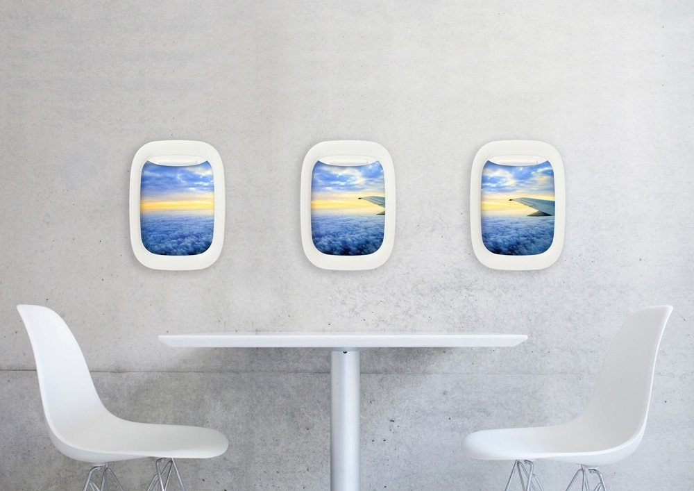Three wall hangings that look like airplane window seats with view of sky and plane wing