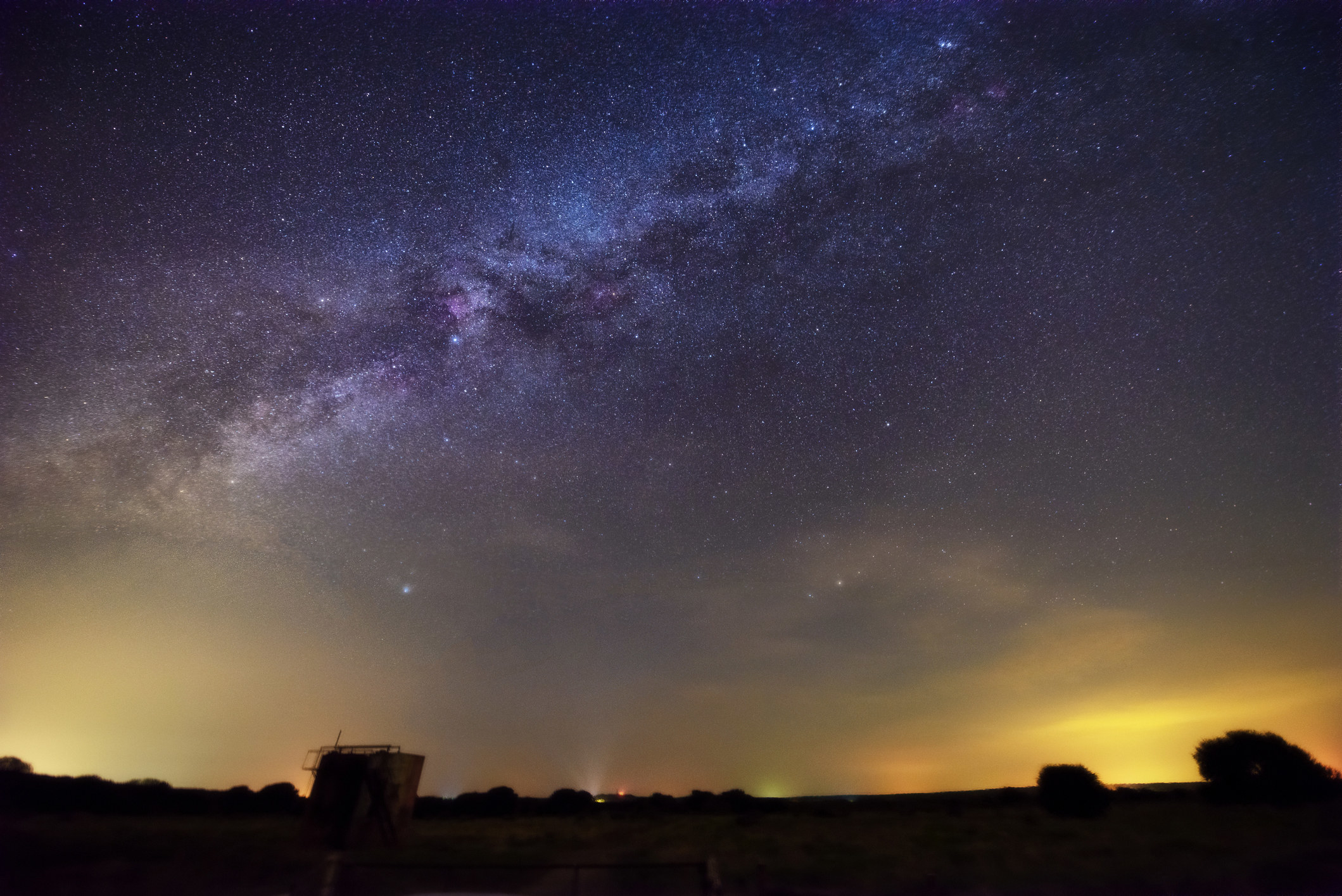 Beautiful night sky with vivid milky way and warm light over the horizon