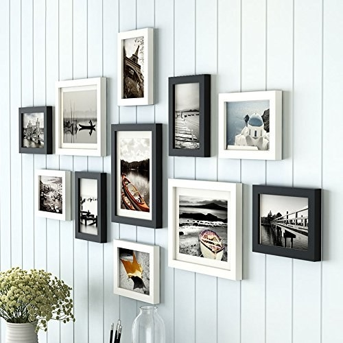 Black and white photo frames hung up on a white wall.