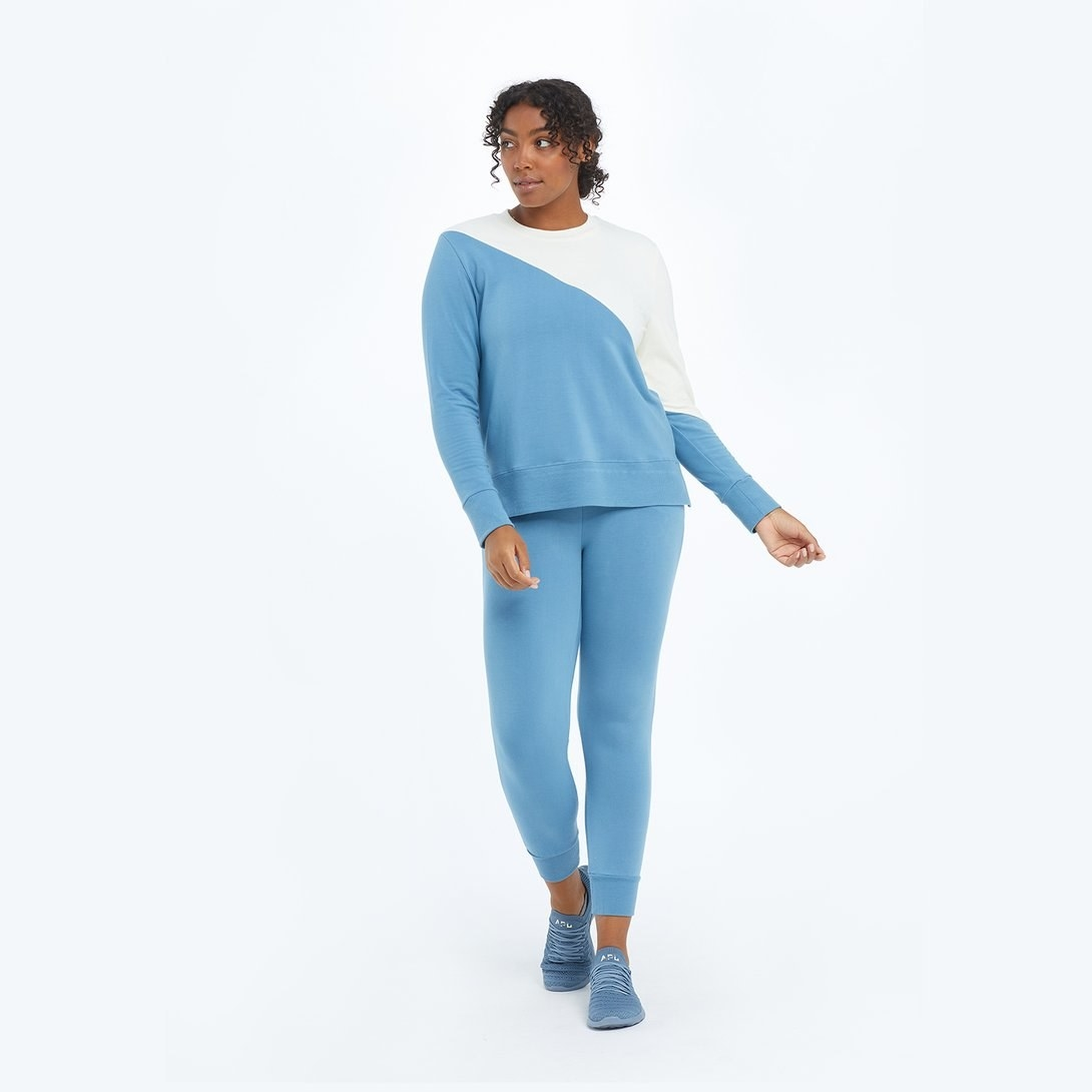 model in light blue joggers and matching diagonally colorblocked blue and white sweater top
