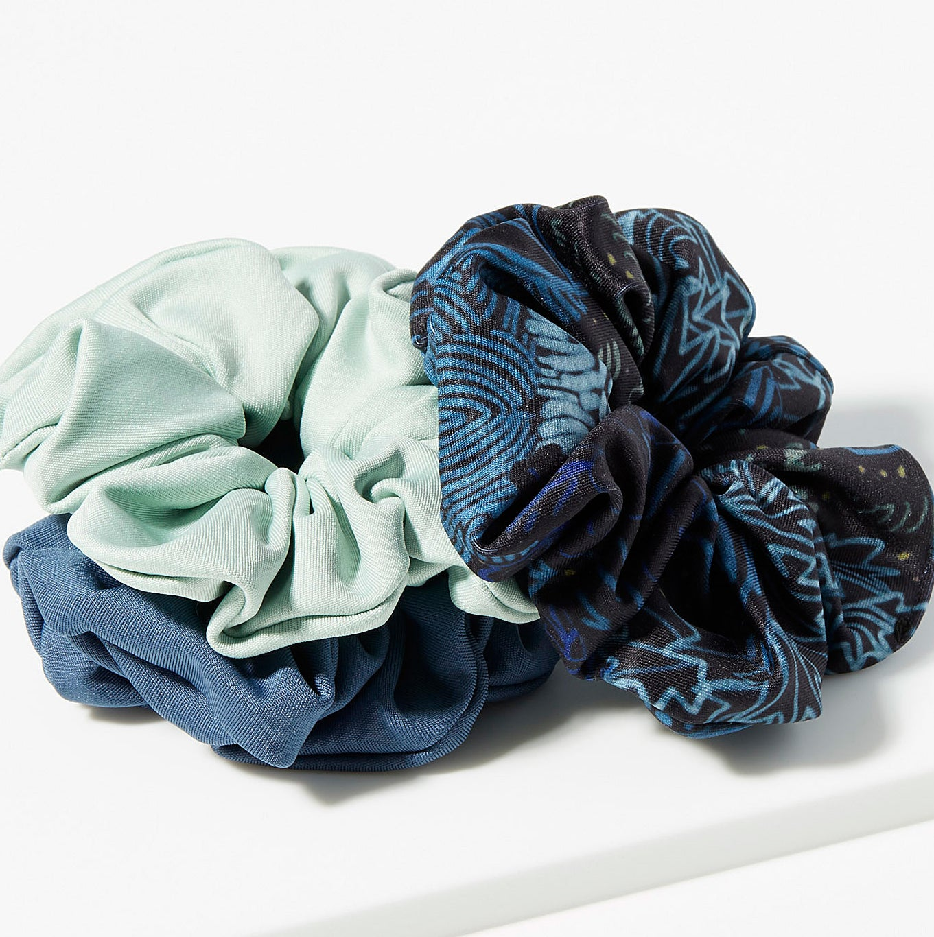 The three scrunchies in a pile on a table