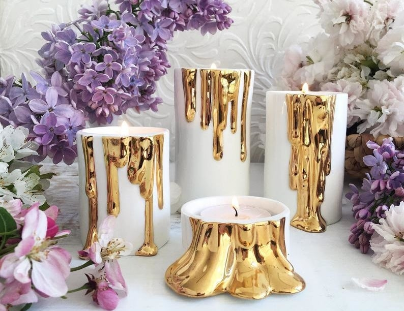 The white and gold candle holders in various sizes — they're white with a gold wax-dripping design