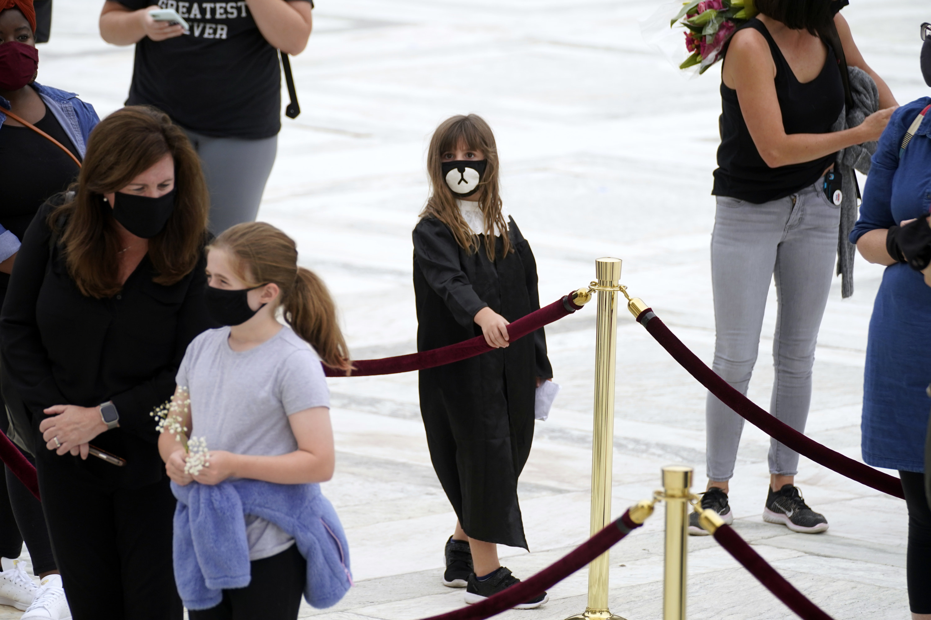 A girl in judges robes with a sad mask stands in line