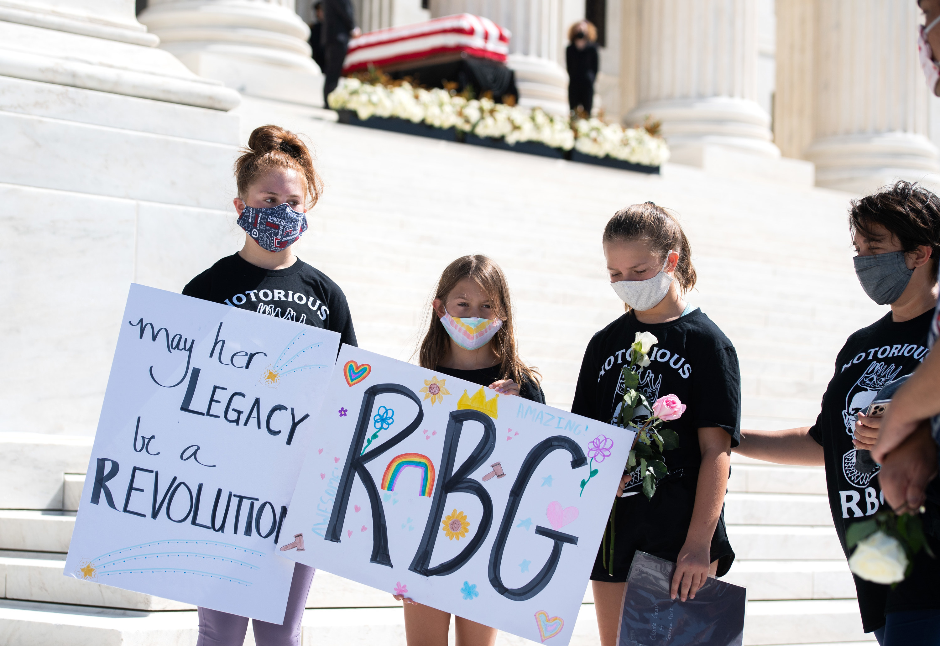 Three girls carry signs saying RGB and may her legacy be a revolution