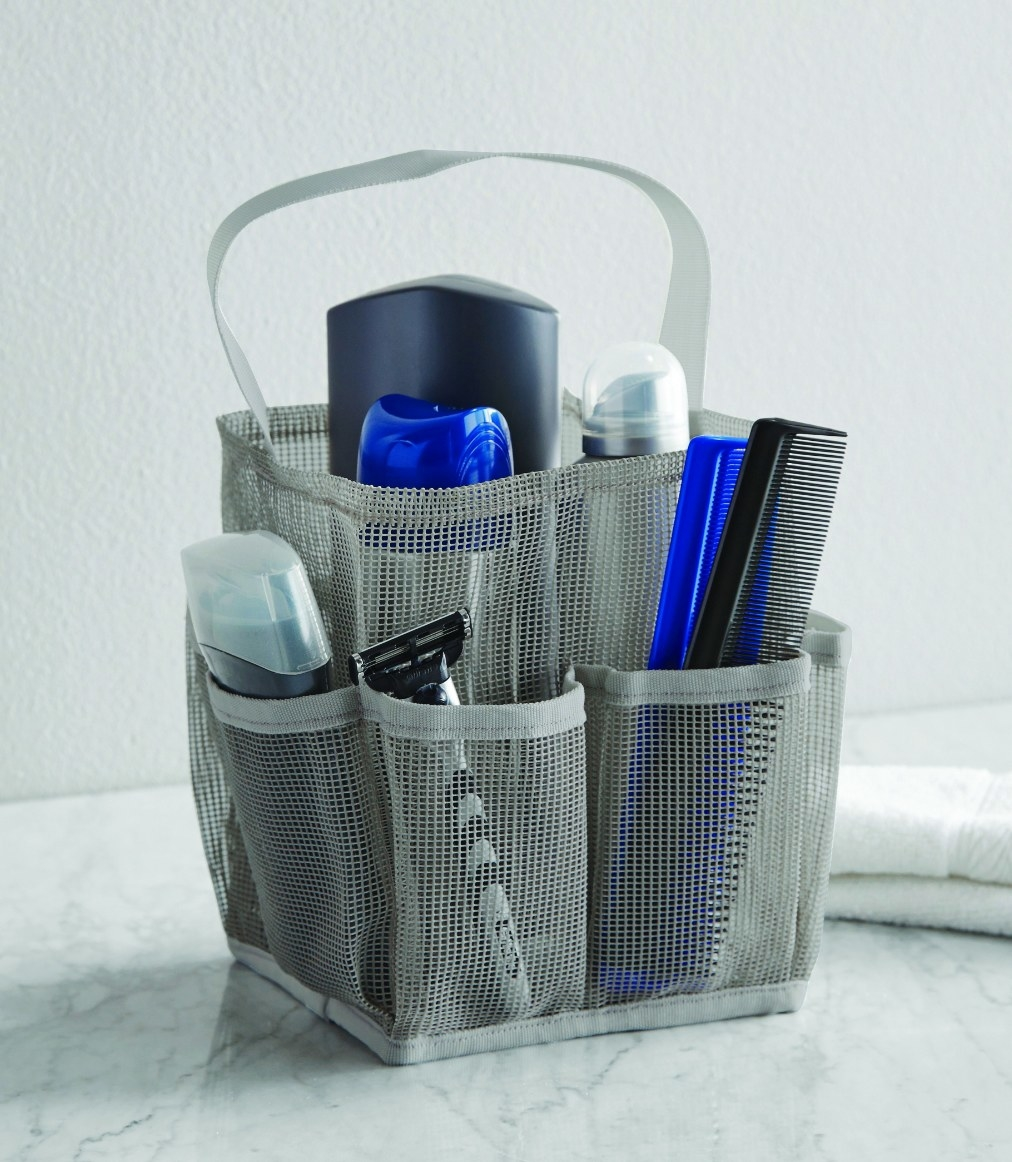 The shower tote being used to hold a razor, deodorant, and combs