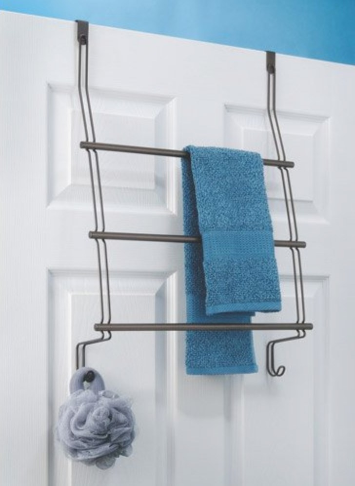 The over the door rack being used to hold a towel and a loofa