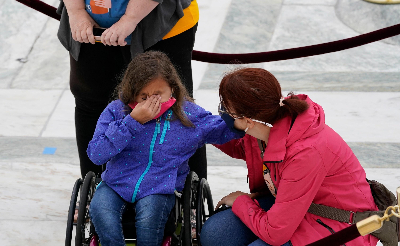 A girl in a wheelchair cries