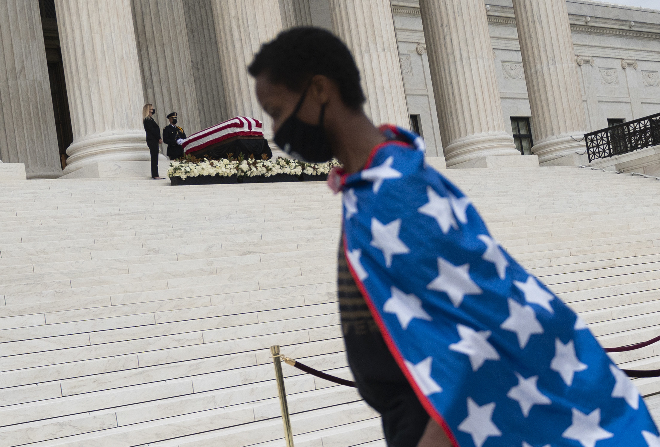 A boy in a flag cape walks in front of where Justice Ginsburg is lying in state