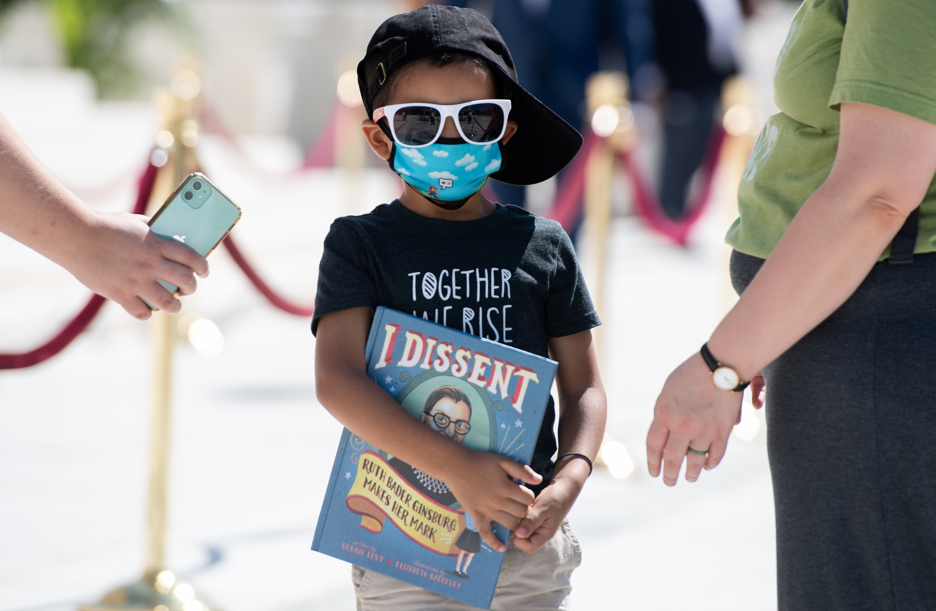 A boy carries a book that says I dissent