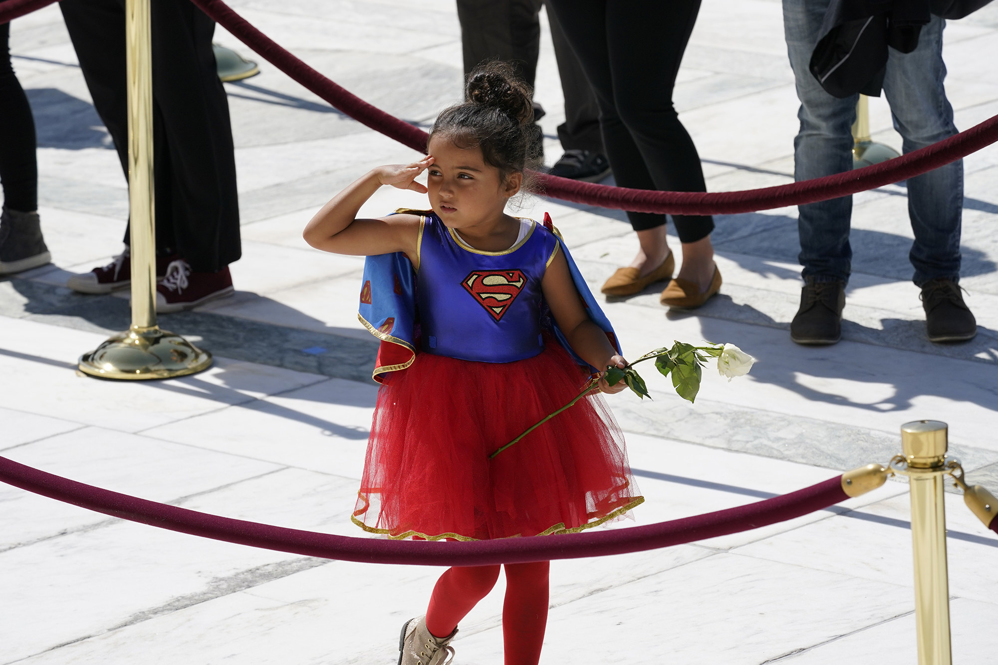 A girl dressed in a Supergirl costume pays her respects at the casket