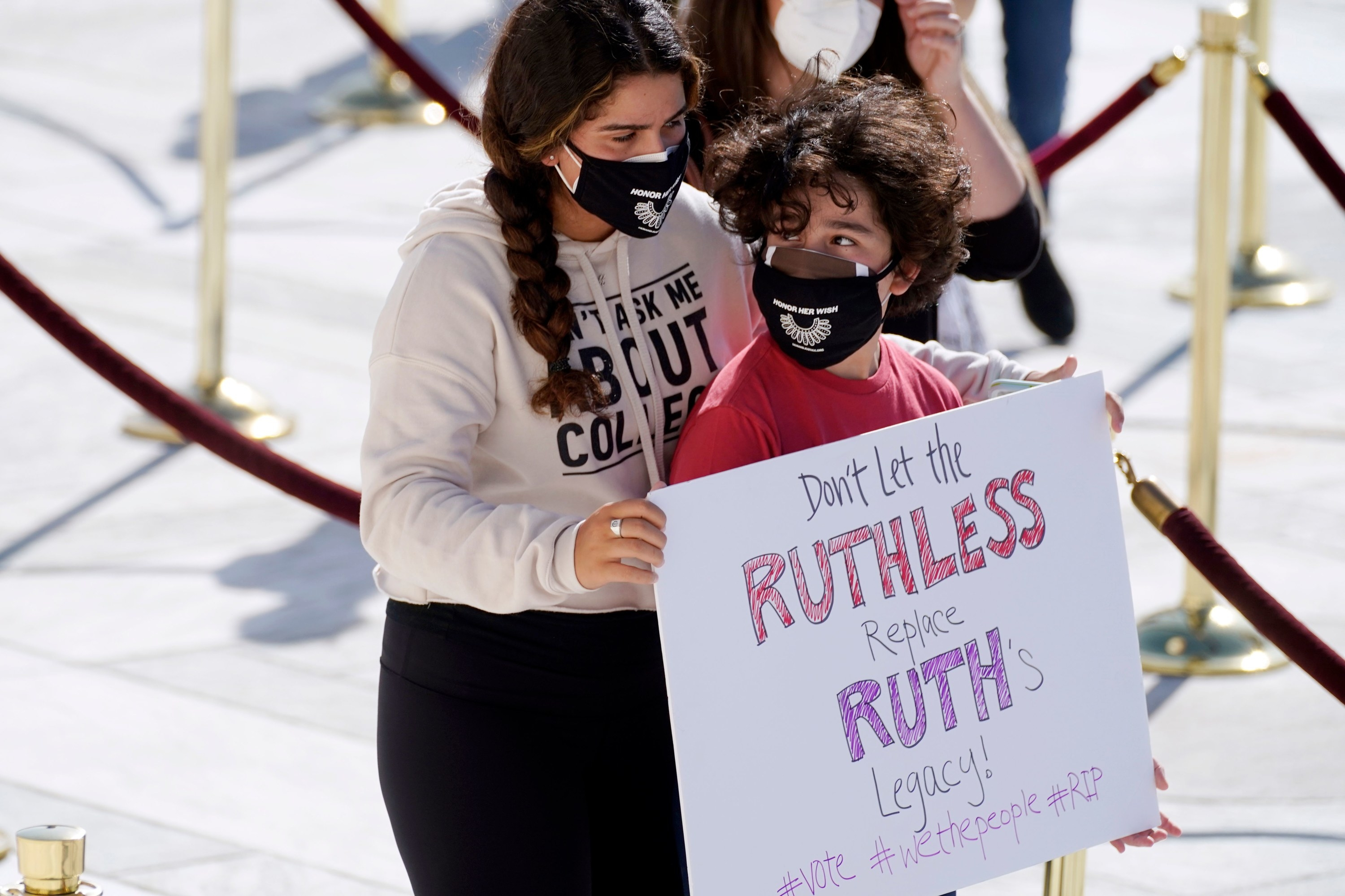 A boy carries a sign that says dont let the ruthless replace ruths legacy