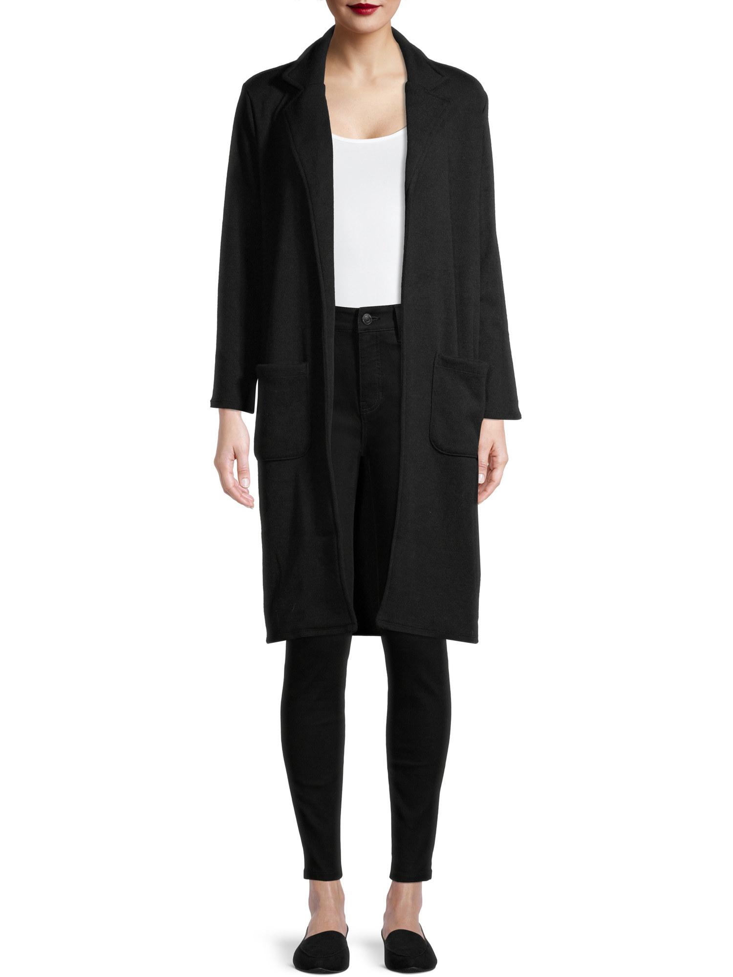 Model wearing a long black cardigan coat, white t-shirt, black jeans, and black shoes