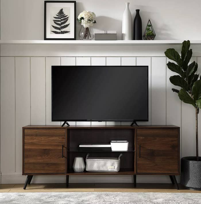 A  dark walnut wood tv console with decor in the center shelves and a TV on top