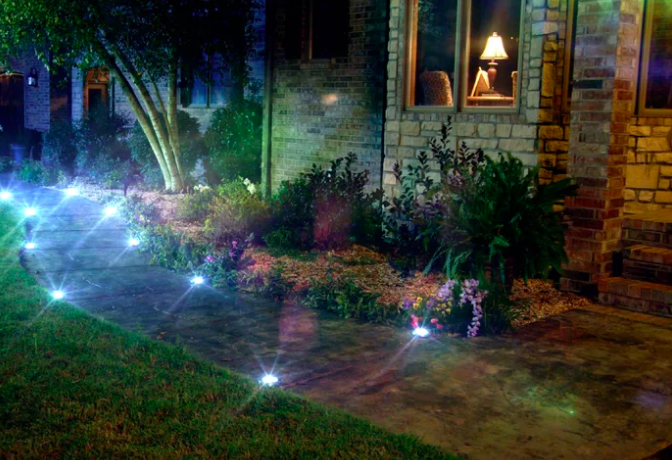 Twinkling circle solar powered pathway lights along a stone pathway next to a home with a garden outfront