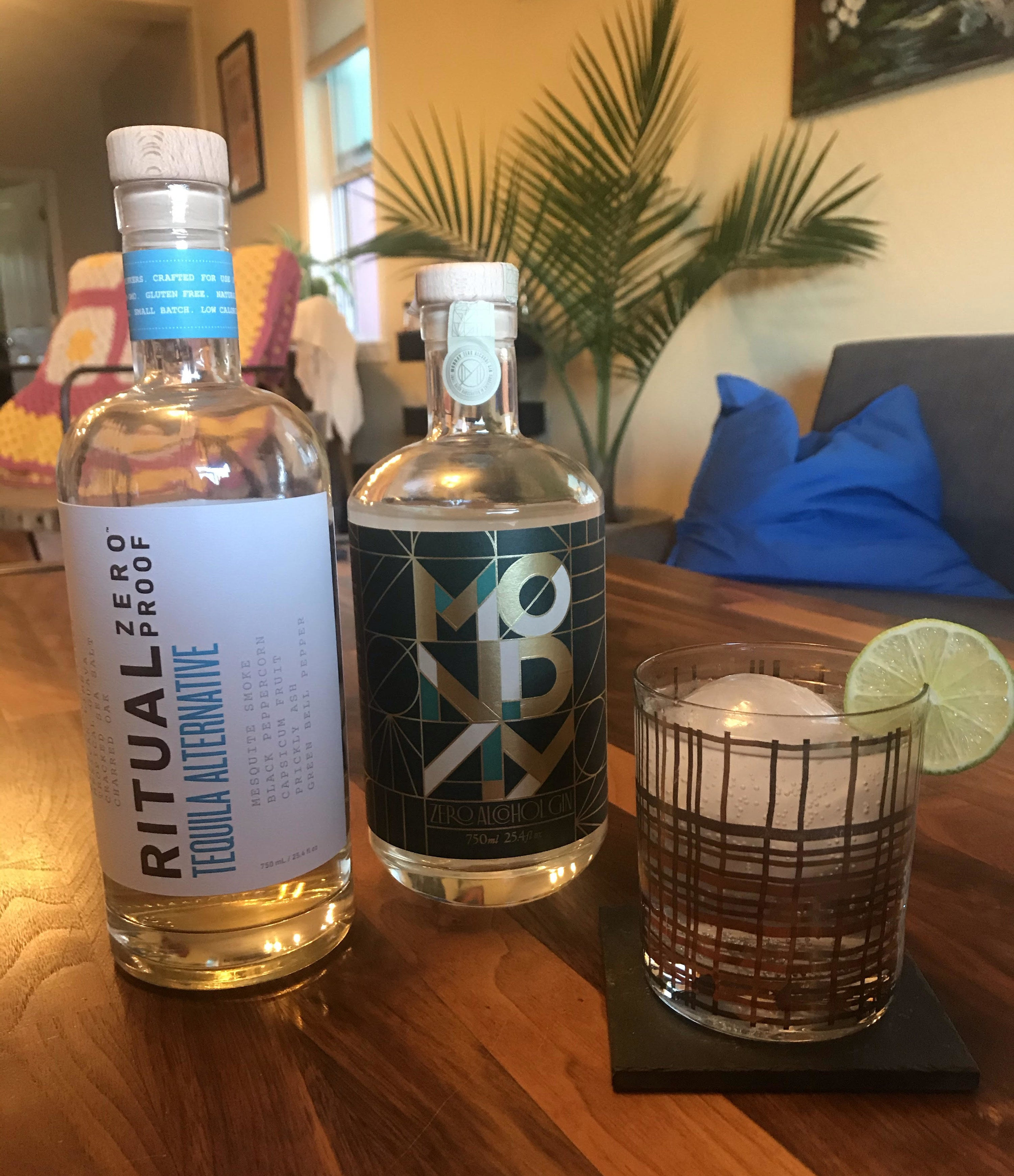 the writer's bottles of non-alcoholic tequila and gin next to a mocktail