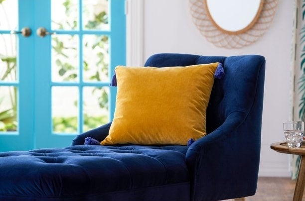 Yellow throw pillow on a navy velvet chaise lounge