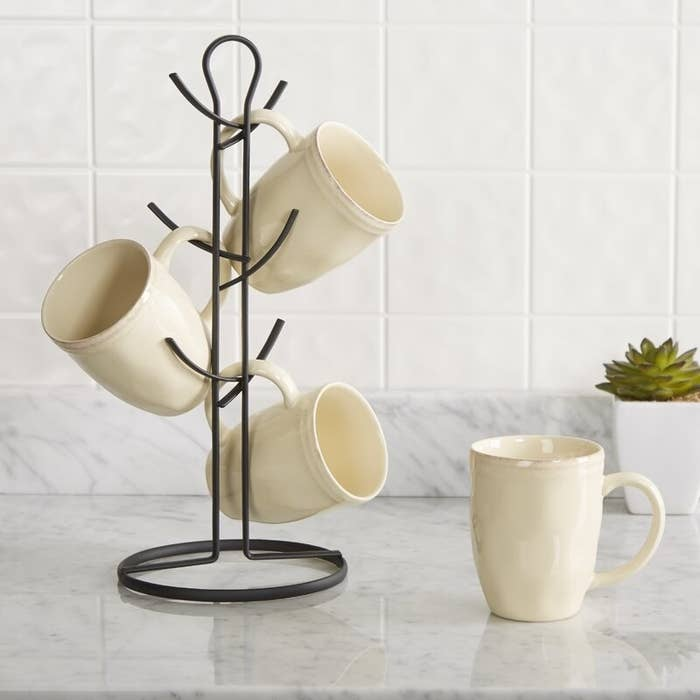 A metal mug tree with six arms that currently holds three mugs on the counter