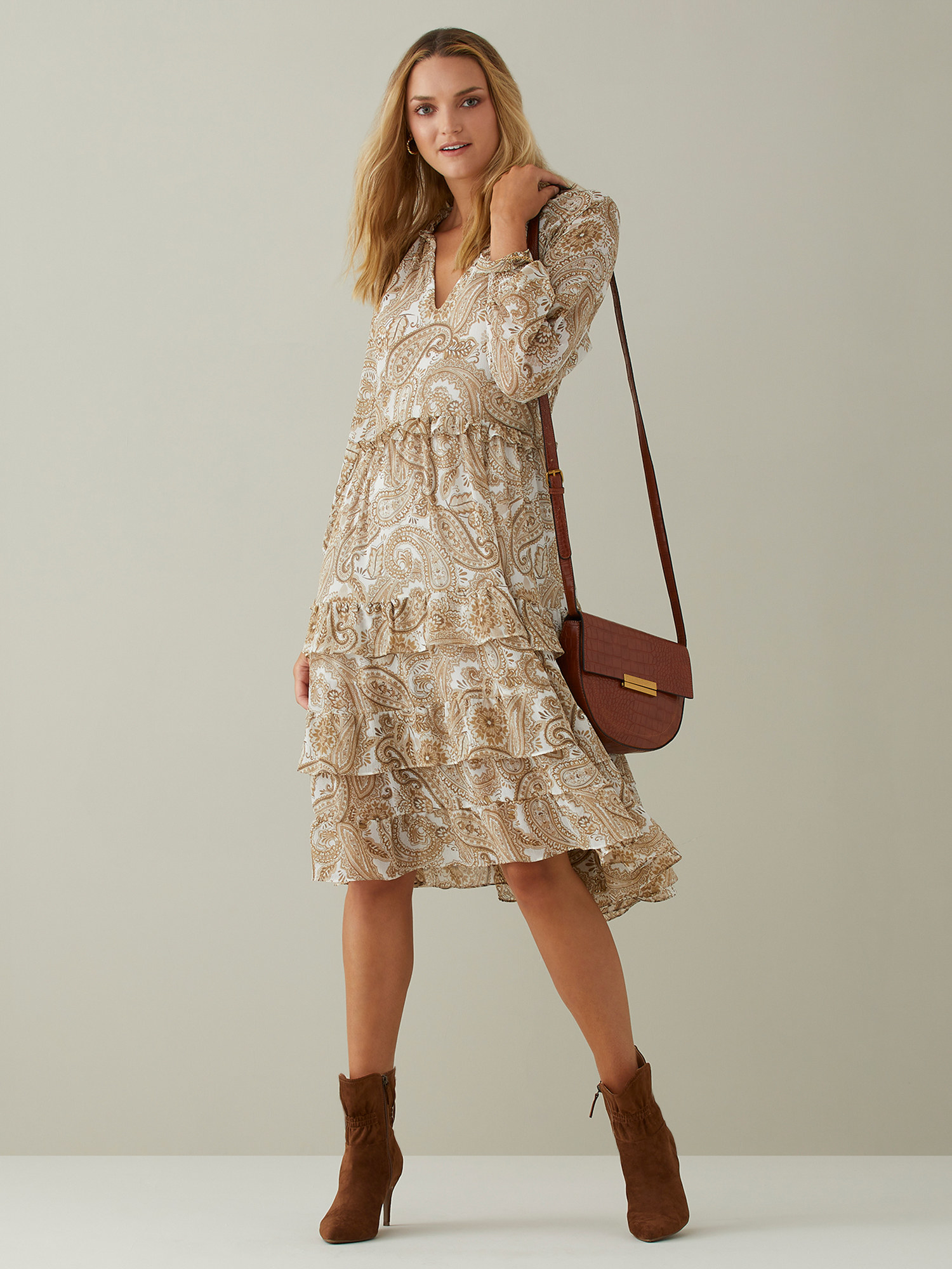 Model wearing the tan dress with paisley print