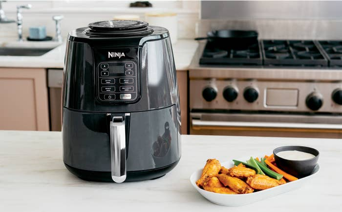 Black ninja air fryer and a plate of buffalo wings on a kitchen counter