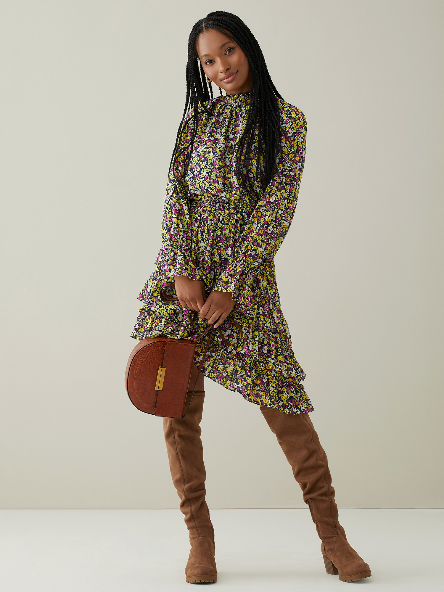 Model wears long-sleeve dress with small green and purple floral pattern