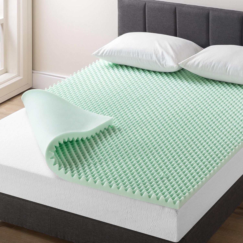 Mint green egg crate memory foam mattress topper on top of a mattress