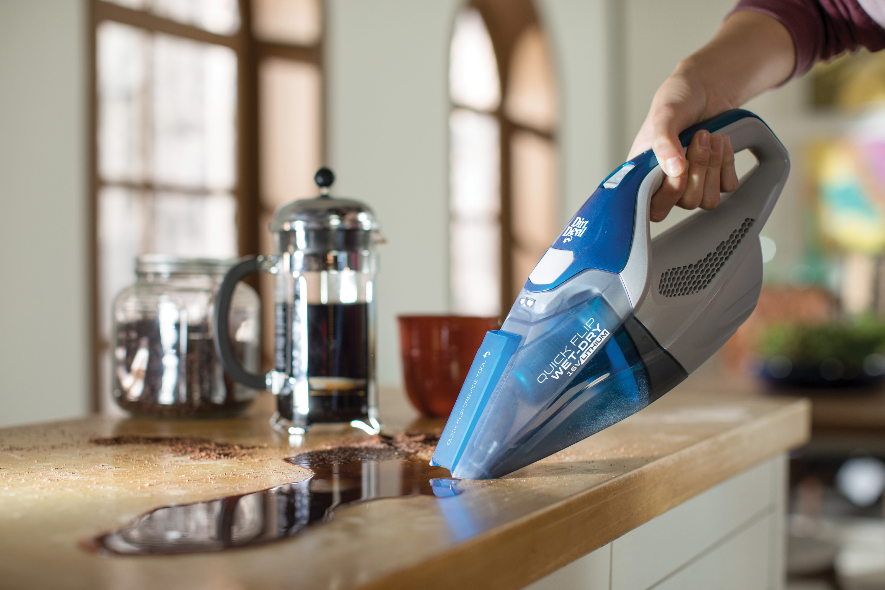 Model using a hand vacuum to vacuum up slipped coffee