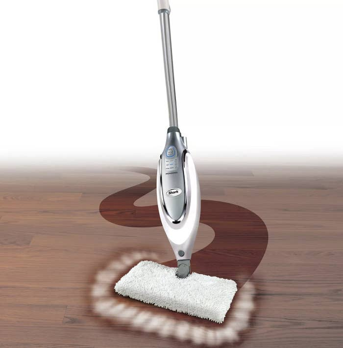 A silver steam mop is being used on a wooden floor to show how it cleans