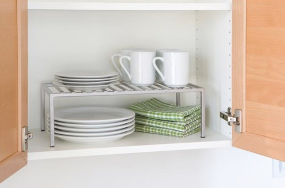 The expandable kitchen shelf organizer being used to hold cups and plates