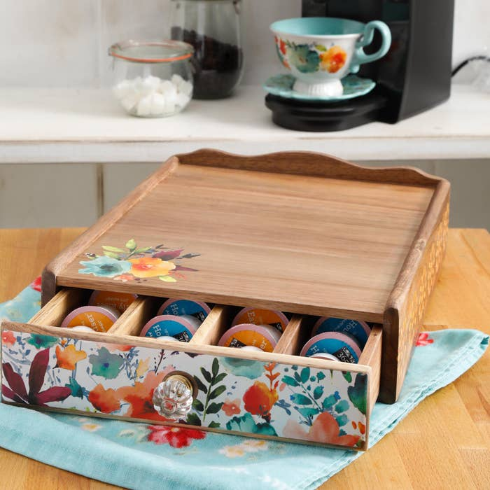 Wooden pod organizer with glass knob and orange, blue, and green flowers
