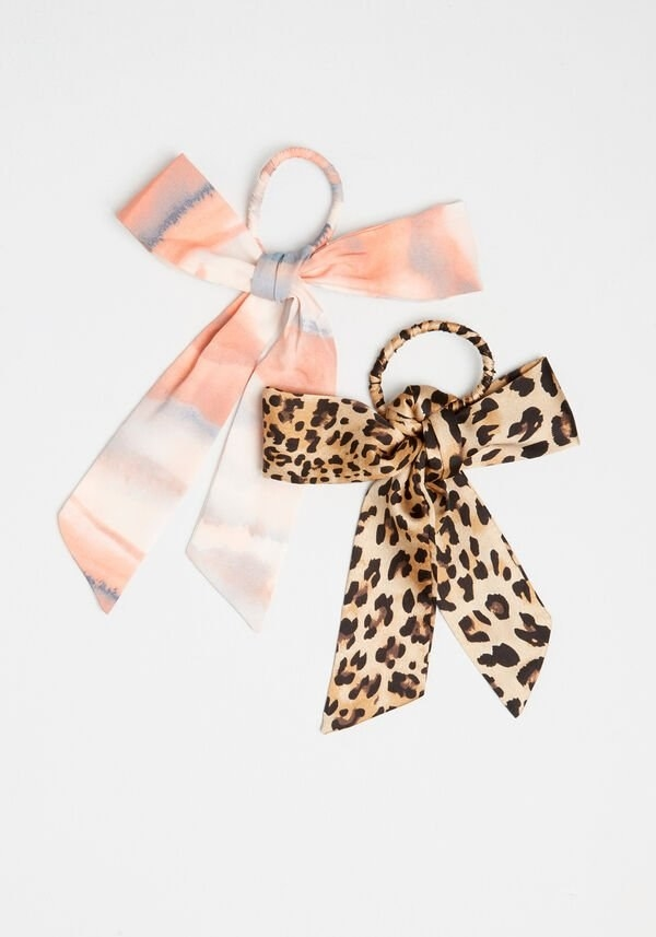 two hair ties with bows attached to them, one is pink and white and the other is leopard print