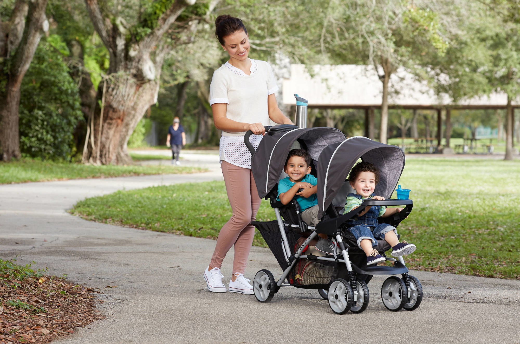 Model pushing a double stroller with two kids in it