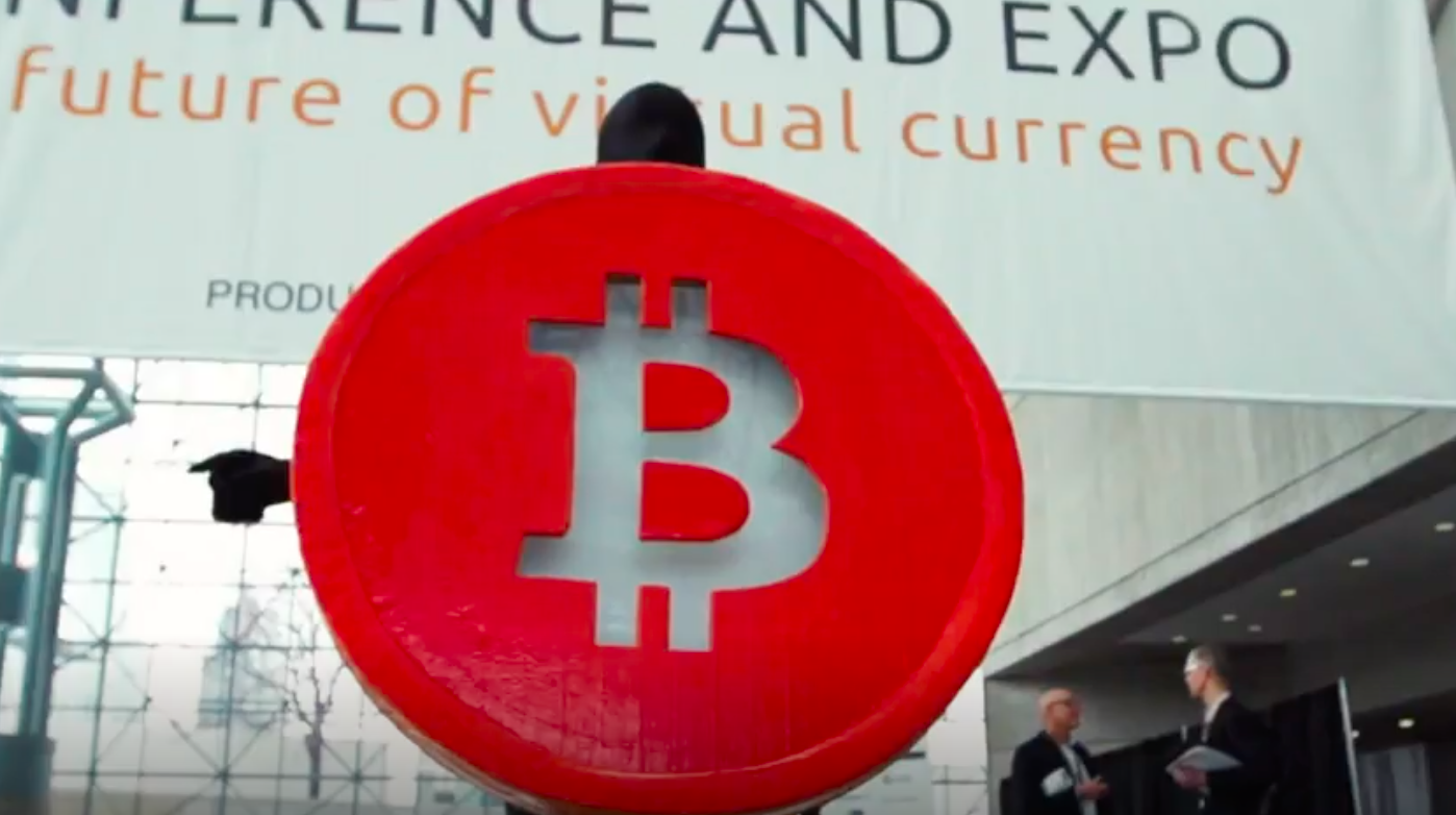 Man wearing a giant red Bitcoin costume