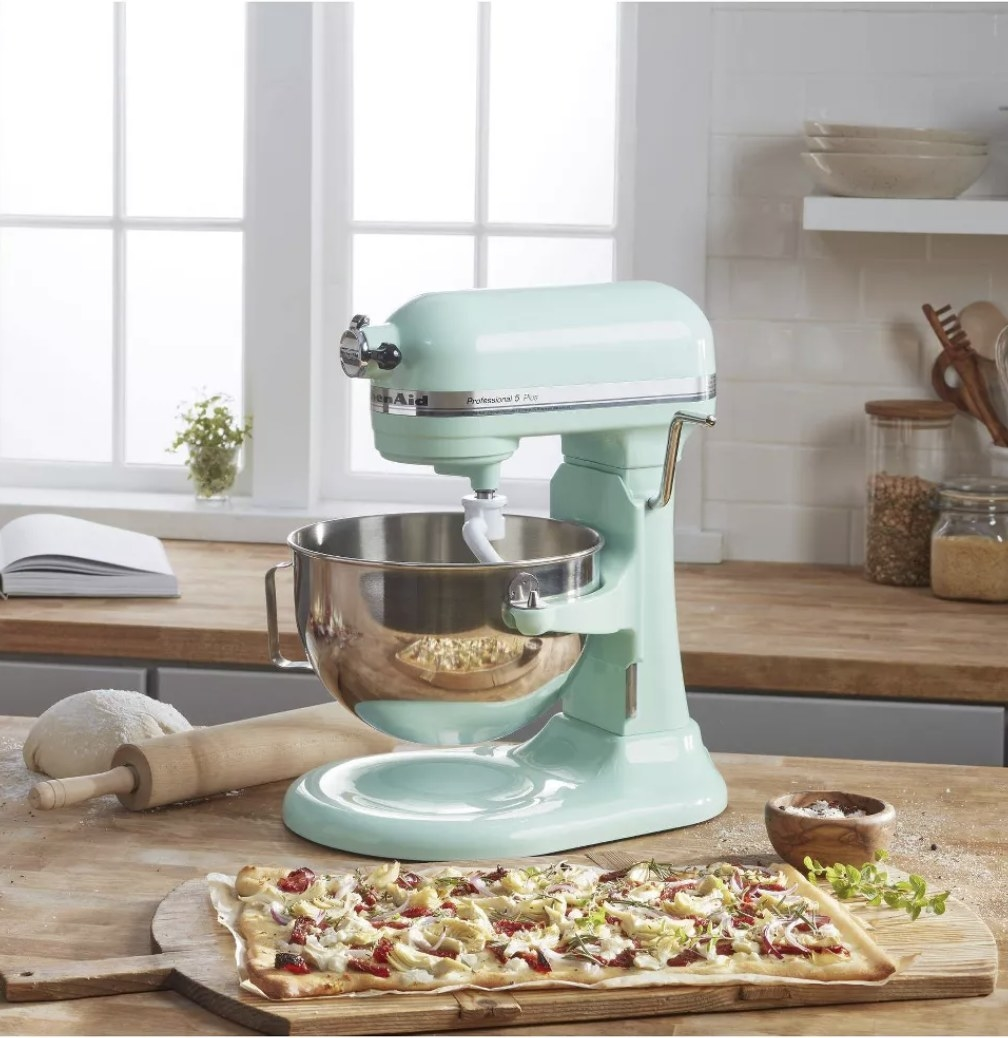 A baby blue Kitchenaid stand mixer next to a flatbread pizza in a kitchen