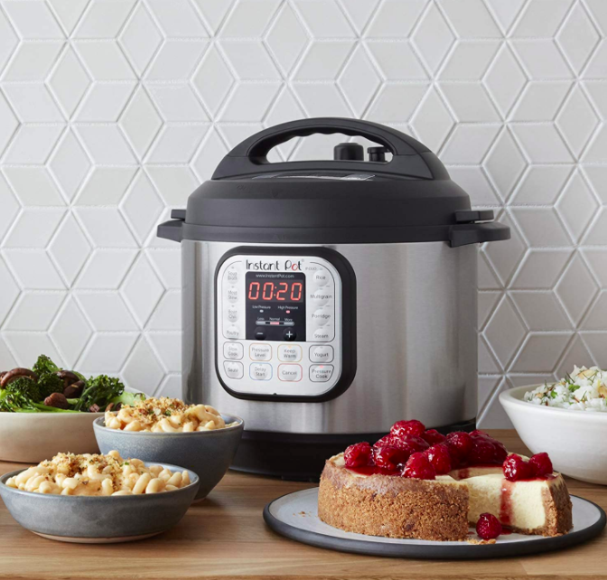 Silver Instant Pot next to bowls of mac and cheese, roasted veggies, and a raspberry cheesecake