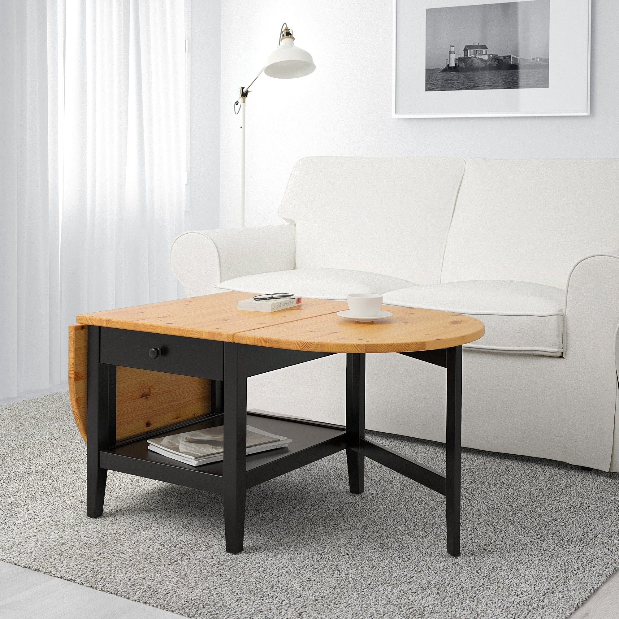 A oval-esque coffee table with one end folded in, leaving that side flat-edged, with a drawer and shelf beneath it. With both ends in, the table would be square