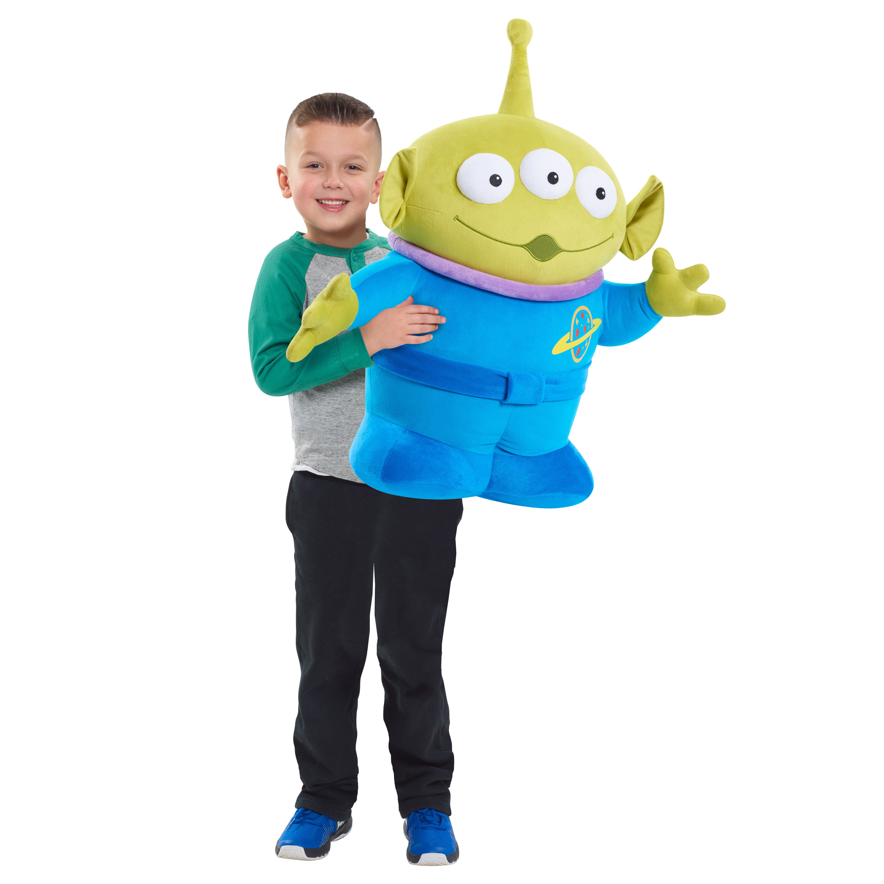 Child model holding up an oversized plush alien toy from Disney's Toy Story 4