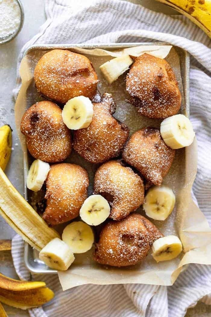 A baking sheet pan with banana fritters garnished with slices of fresh banana slices.