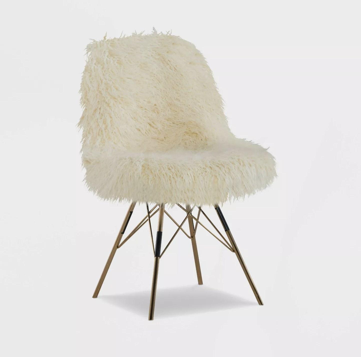 A cream faux fur chair with gold chrome legs