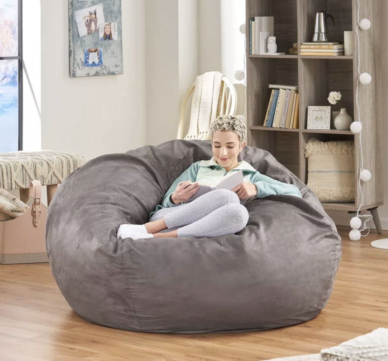 Model is sitting on top of a faux suede grey bean bag reading a book