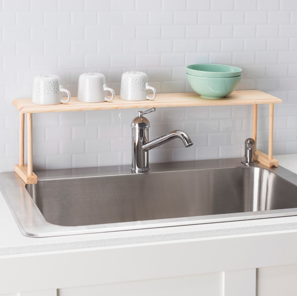 The over-the-sink organizer holding cups and bowls