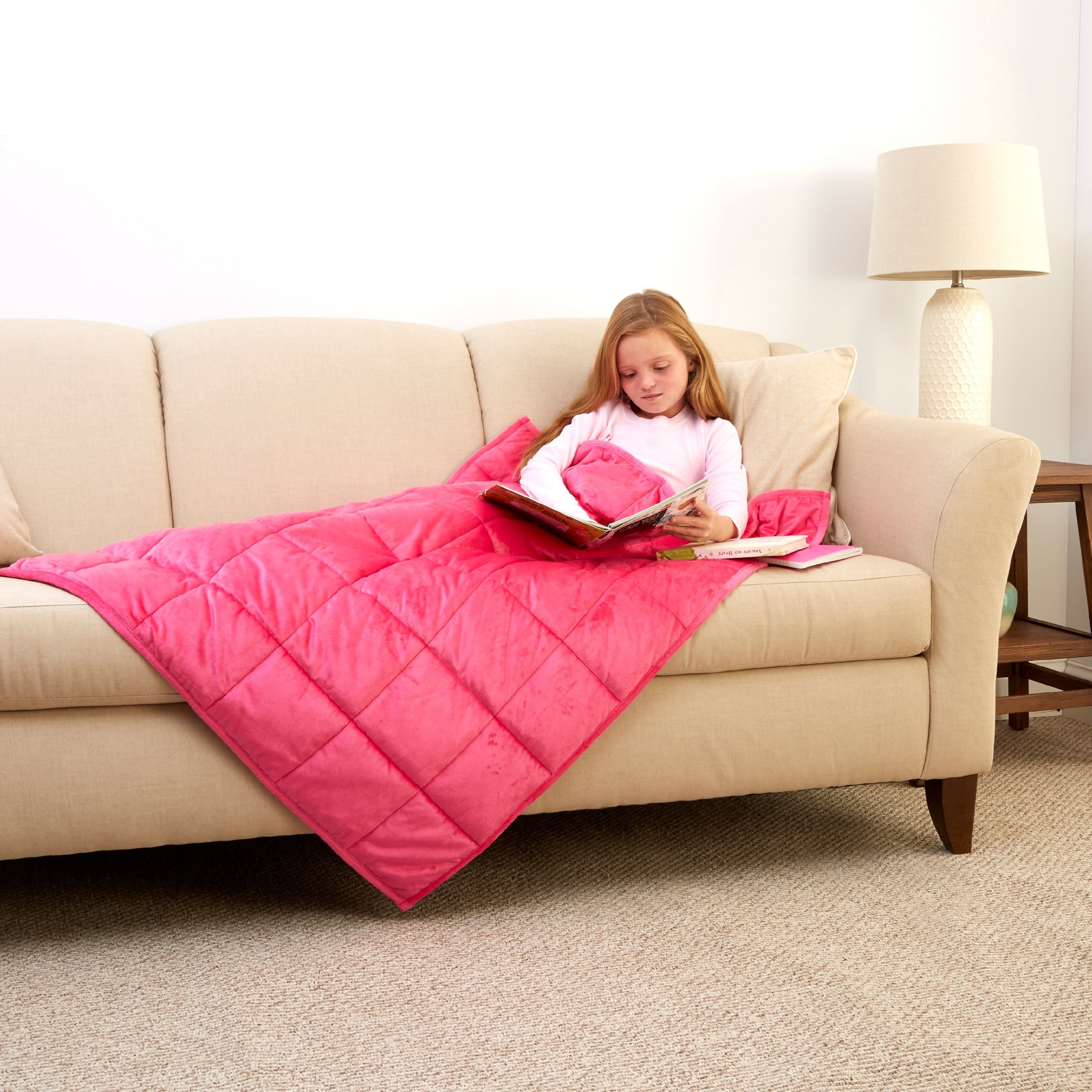 Child model sitting on the couch and reading with a pink weighted blanket on top of them