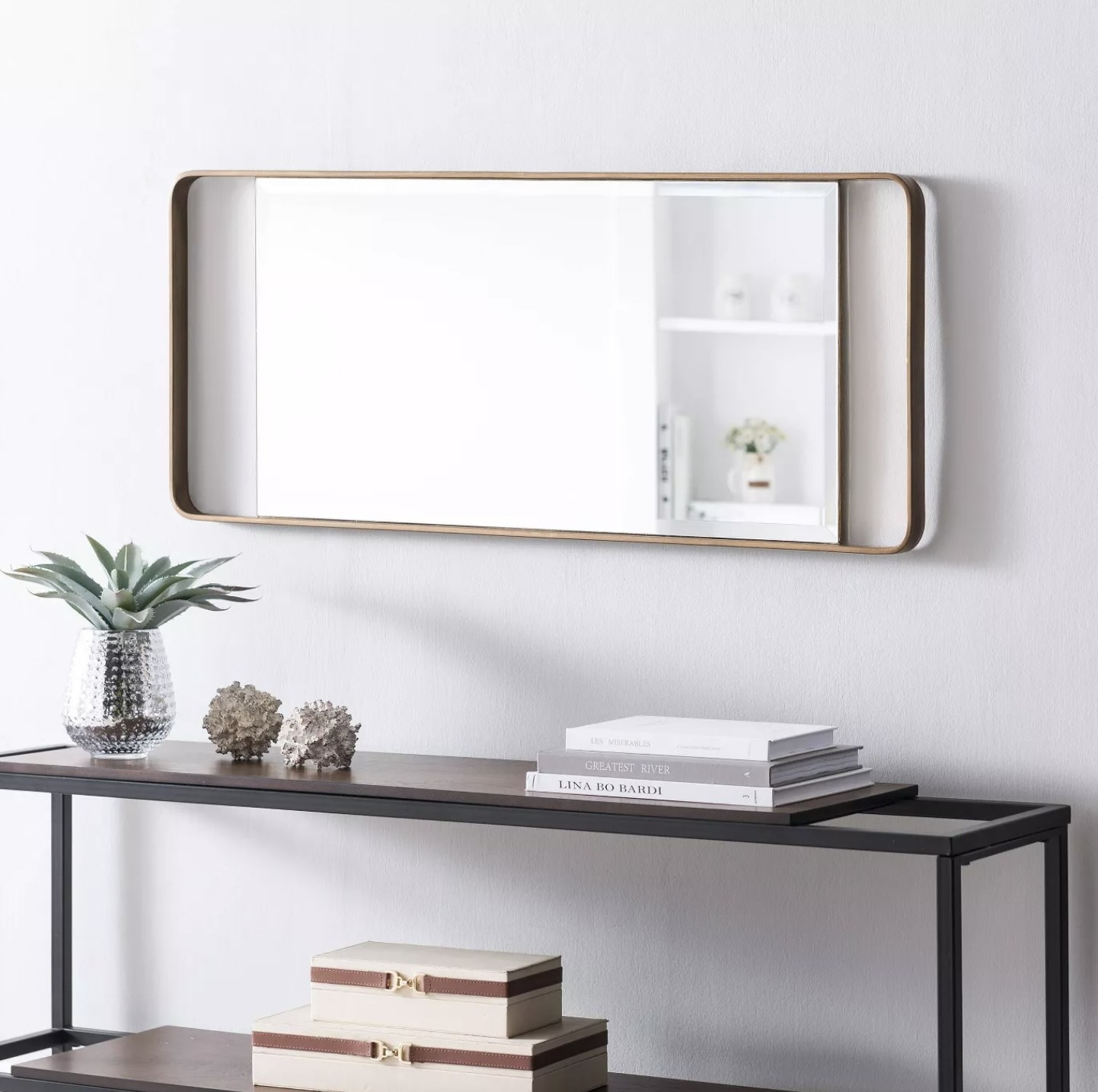 A rectangular leaning mirror with a gold finish hung up on a wall in a home