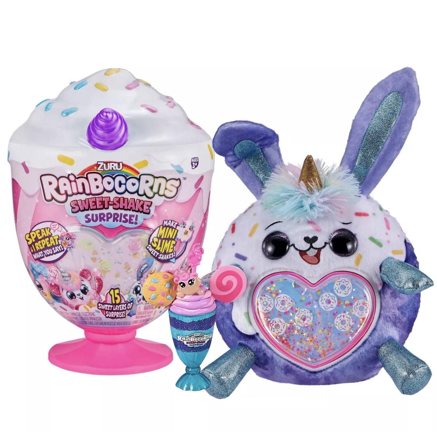 A purple rainbocorn sitting next to a milkshake-shaped toy