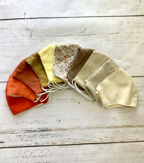 Autumn-toned face masks in orange, red, brown, green, yellow, and more shades in a neat circle arrangement