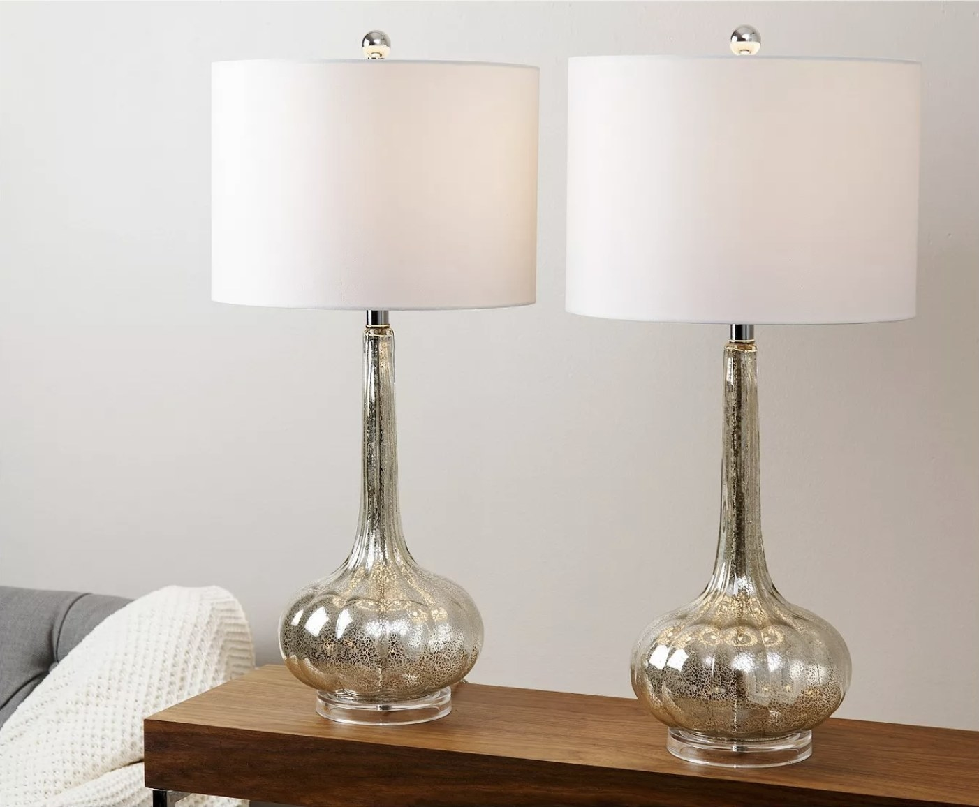 A set of two table lamps in a living room with an antique glass base and white shades