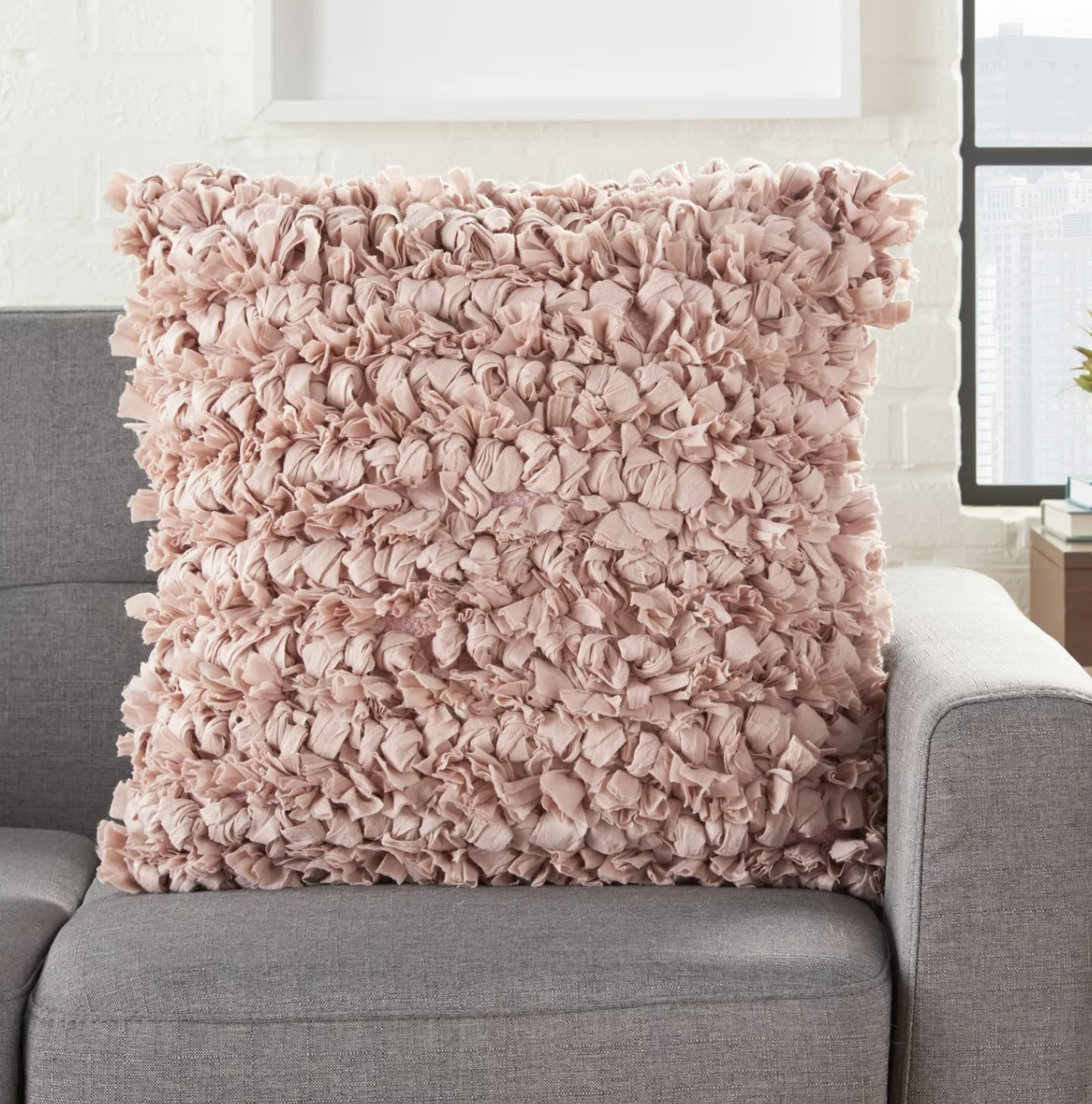 A blush pink loop shag throw pillow on a couch
