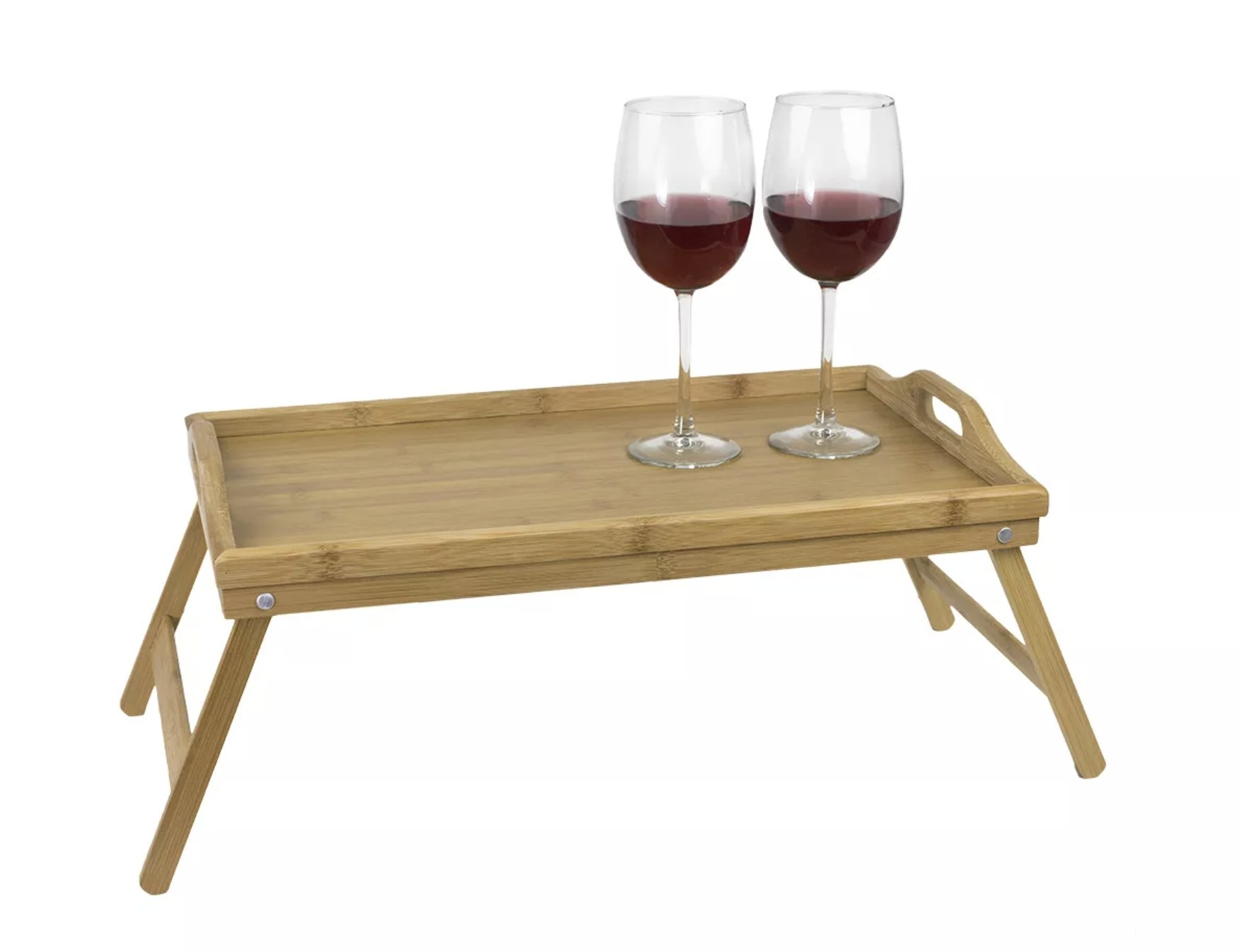 A light pine wood folding bed tray with handles and two wine glasses on top
